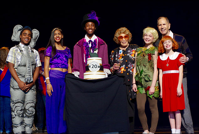 Students dressed as characters from Music Theatre International's Broadway Junior titles of musicals present a cake honoring the 20th anniversary of Broadway Junior.