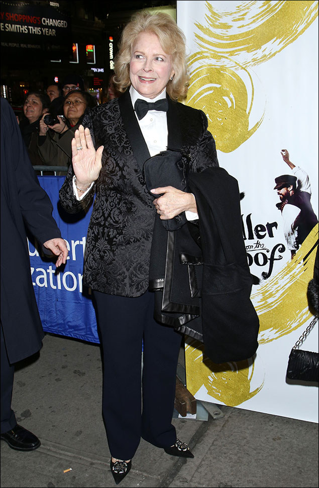 Candice Bergen was fabulous in her black-on-black brocade tux! From the bow-tie and the shawl collar down to her embellished slippers, she was style personified. And her Hollywood savvy on the red carpet circuit taught her to slip off her outerwear so the photographers could snap up her glamour!