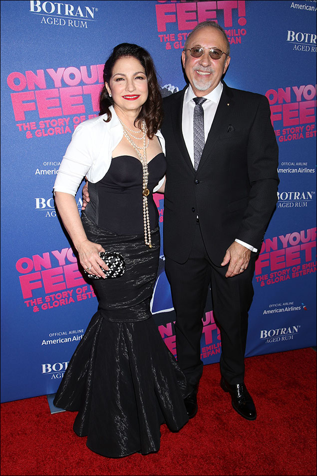 Gloria and Emilio Estefan celebrated their night greeting friends and fans alike! A perfect pairing of formal black and white, but easy and cool the way two salsa stars make beautiful music together! His matte tux and metallic tie worked perfectly with her black-over-black mermaid gown! The white bolero shrug and the cascading pearls were only outshone by Gloria's sparkling eyes and that radiant smile. And I love the Habanero-red lips!