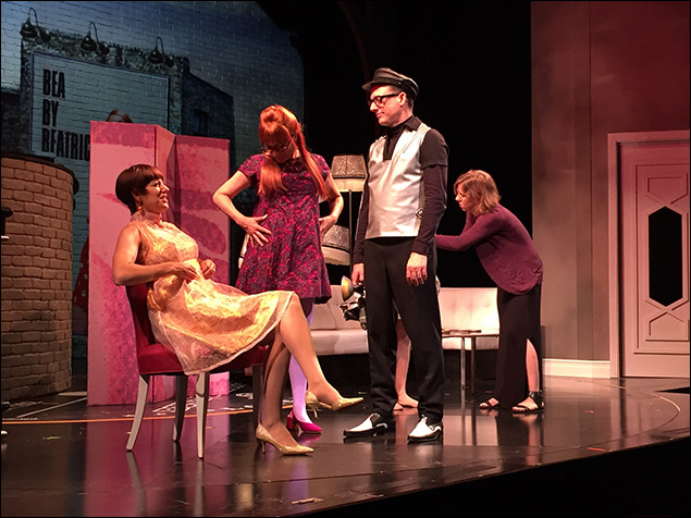 """Nicole Parker (as Bea), Kate Blumberg (as Frida), and Brad Heberlee (as a """"Photographer"""") hold on stage as costume designer Jessica Ford works in the background."""
