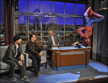 U2's the Edge and Bono watch as Spiderman drops in for a visit on July 18, 2011