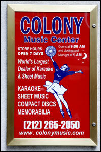 A sign that used to appear at Colony, featuring the iconic cheerleader character, holding aloft a vinyl LP.
