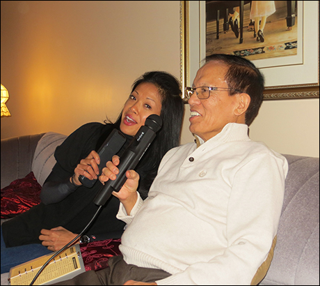 """J. Elaine Marcos: """"With my Dad, Christmas 2013, a little karaoke at home with the Magic Mic! It's a staple in every Filipino home."""""""