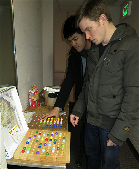 Sam Rogers and Raymond Interior ponder a Sodoku puzzle on the treat table.
