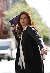 Debra Messing's Julia tosses a copy of <i>The Singing Bird</i> at Peter.