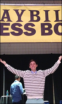 Student reporter Brennan Felbinger in front of the Playbill Press Box at the Junior Theater Festival.