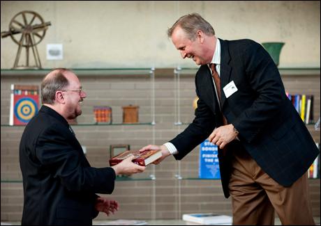 Playwright Rupert Holmes accepts a gift from novelist John Grisham