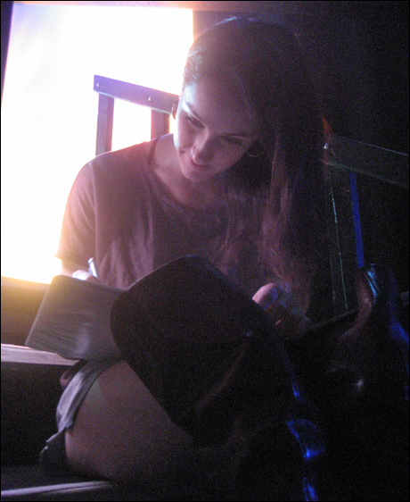 Laura Hall reads her Swing Notes by the light of the stage, the only warm place in the theatre.